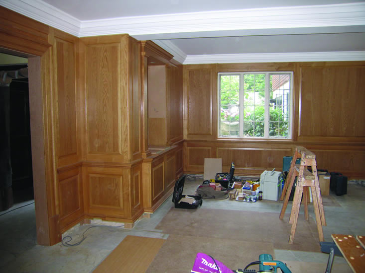 Oak panelling & display cabinet undergoing installation
