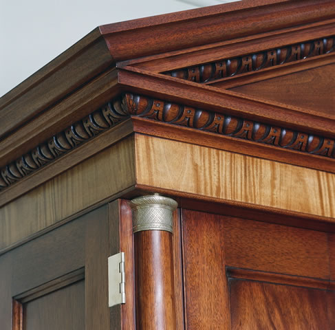 Pedimented cabinet, brass capitals, satinwood banding, hand carving