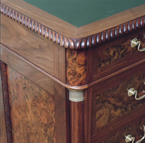 Hand carving to top, burr detailing & brass capital to walnut desk