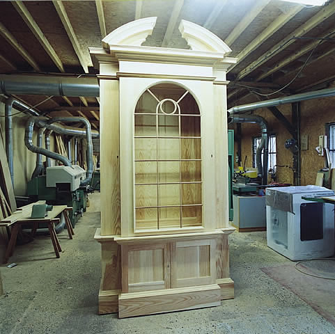 One of 4 pedimented, glazed door bookcases, awaiting painting